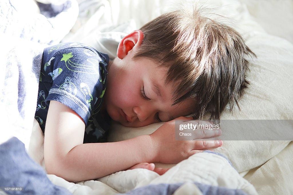 Yougn Boy Sleeping on his bed : Stock Photo