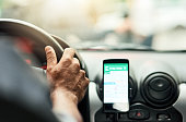 Closeup shot of a man using a phone to find directions while driving