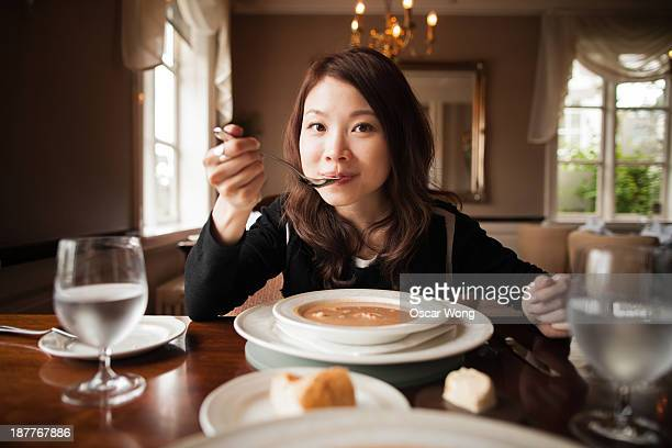 A youn girl is having soup in a posh restaurant