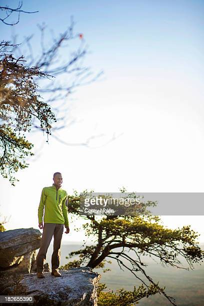 A youn man smiles while looking off a rock overhang at Cheaha Mountain.