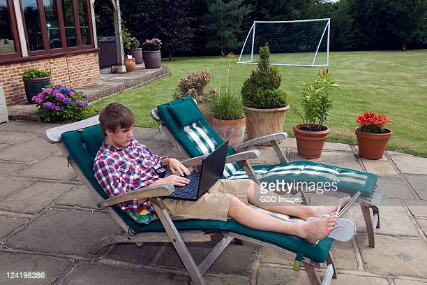 Young 15 year old student on laptop in garden