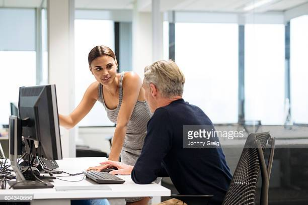Young Aboriginal Australian businesswoman in office with male colleague