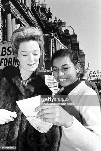 A young Aboriginal girl hands a how to vote card to a voter at polling booth at Sydney Town Hall during the 1967 referendum A sweeping majority of...