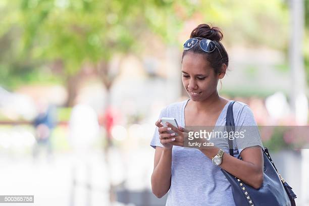 Young Aboriginal woman texting