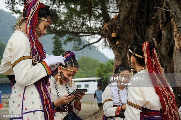 Young aborigines of the Taroqo Tribe play with their smart phones before starting a traditional dance on a stage in Hualien County Taroqo aborigines...
