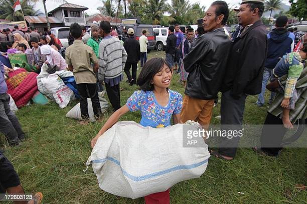 A young Acehnese quake victim carries relief goods during distribution in Blang Mancung in the highlands of Aceh province on July 4 2013 where many...