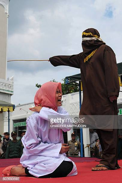 A young Acehnese woman is caned in public a punishment under the Islamic sharia law under the offence of 'khalwat' or 'close proximity' between a man...