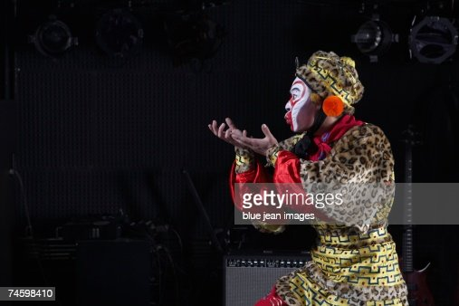 Young actor dressed as Monkey King poses on stage in front of an amplifier and stage lights.