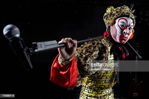 Young actor dressed as Monkey King poses on stage with a microphone and microphone stand.