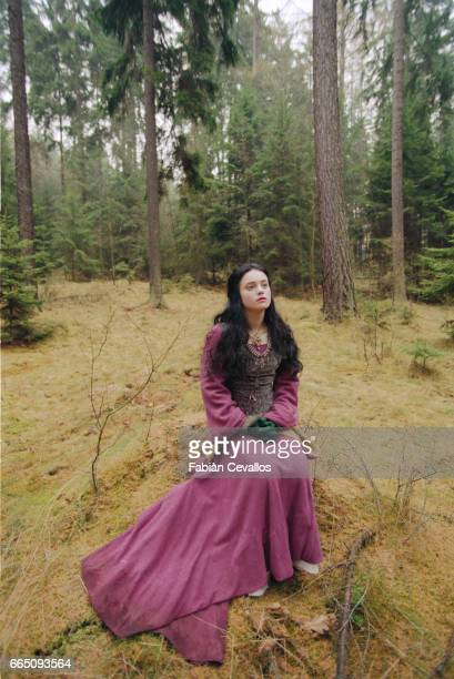 Young actress Monica Keena playing Lilliana Hoffman and wearing an aristocrat's dress sits in the middle of a forest with trees behind her on the set...