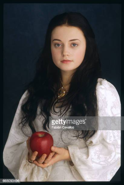 Young actress Monica Keena wearing a white dress poses as Lilliana Hoffman with a red apple in her hands on the set of the movie Snow White A Tale of...
