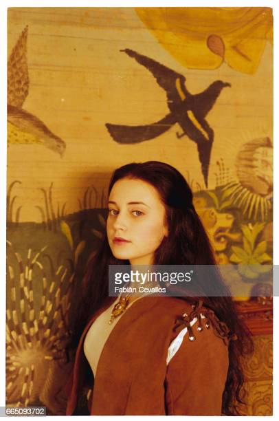 Young actress Monica Keena wearing an aristocrat's dress poses for a portrait with a tapestry on the wall behind her on the set of the movie Snow...