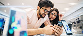Young adorable couple is checking out phone in a bright store.