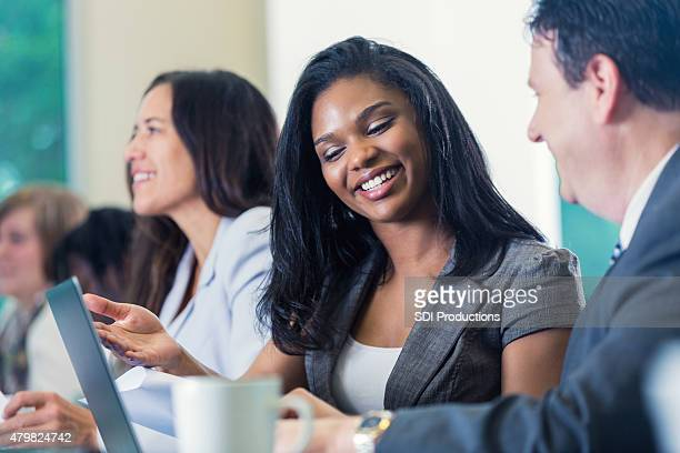 Young adult African American businesswoman using laptop during conference