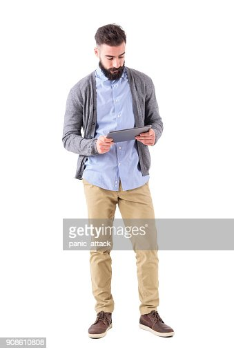Young adult bearded hipster holding and watching at tablet computer. : Stock Photo