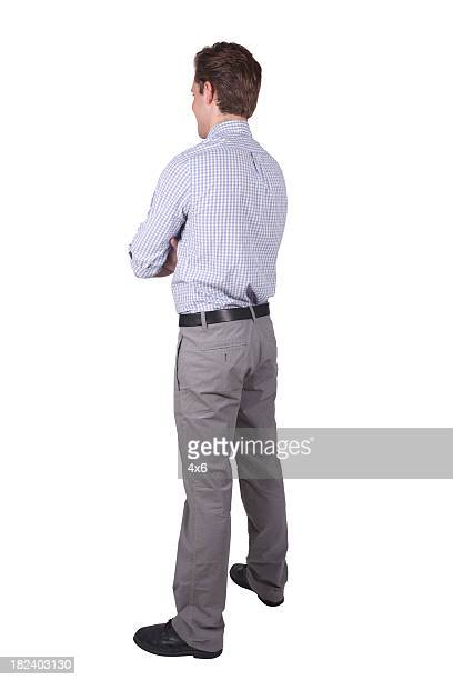 Young adult businessman facing away arms folded
