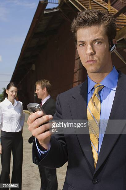 A Young Adult Businessman Using a Headset Cellular Phone, Front View, Waist Up