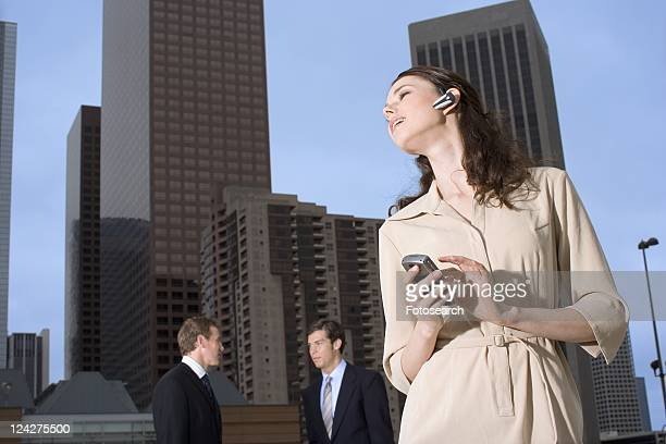 A Young Adult Businesswoman Talking on a Cellular Phone Headset, Low Angle View, Front View, Waist Up