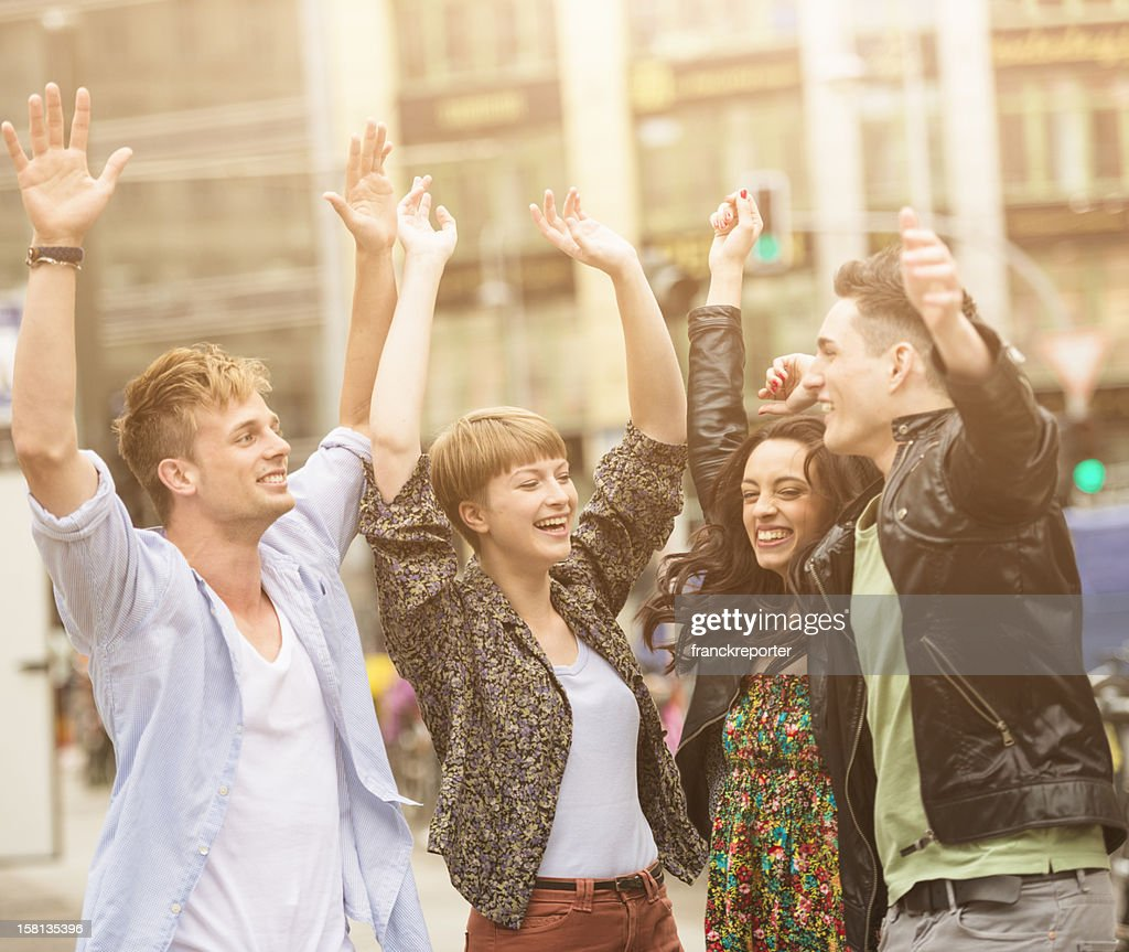 Young adult casual friends outdoors embracing with arm raised : Stock Photo