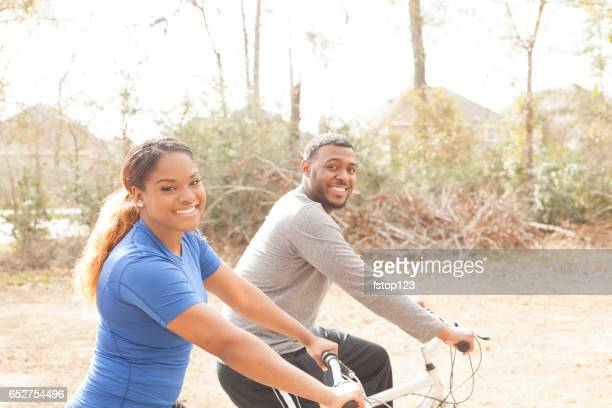 Young adult couple enjoy biking in neighborhood park.