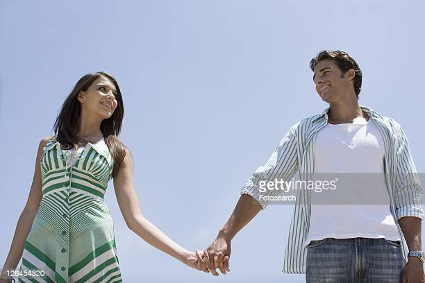 Young adult couple holding hands, Low Angle View