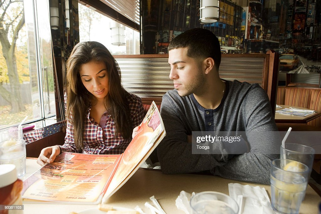Young adult couple looking at menu in diner : ストックフォト