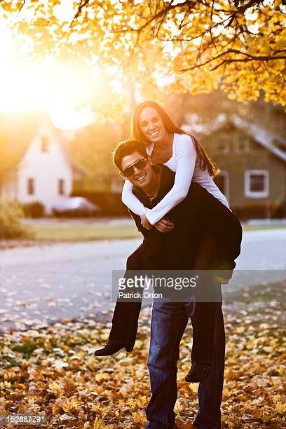A young adult couple smiling while piggy back riding at sunset surrounded by fall colors in Idaho.
