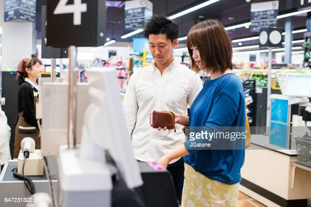 Young adult couple using a self checkout machine