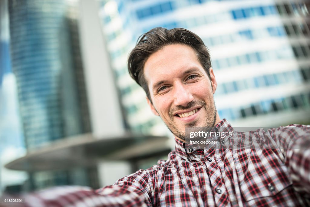 young adult entrepreneur doing a selfie on the city