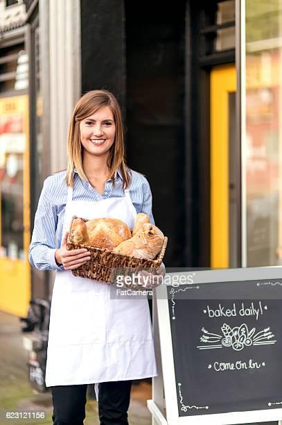 Young adult female baker holding freshly baked goods