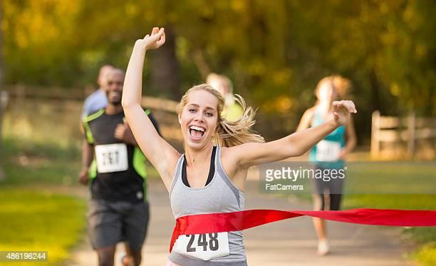 Junge Erwachsene weibliche Überqueren der Ziellinie