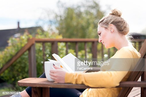 Young adult female drinking coffee and reading a book outside
