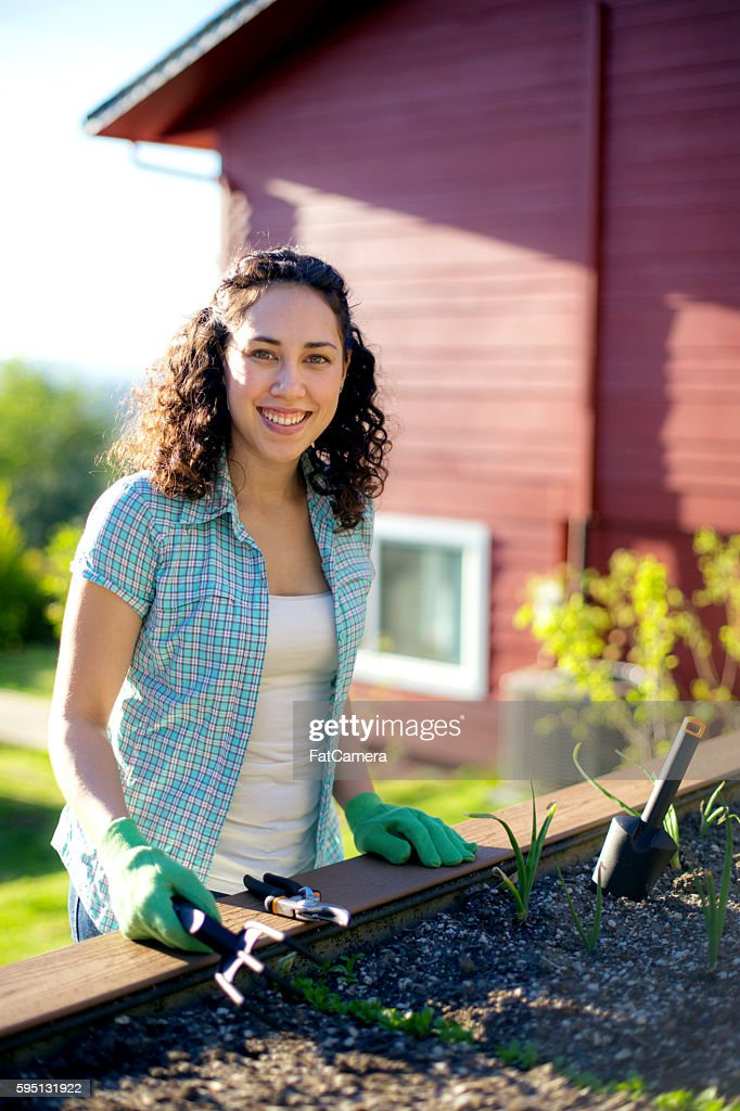 Young adult female gardening outdoors in the sunshine