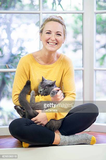 Young adult female holding her precious grey house cat