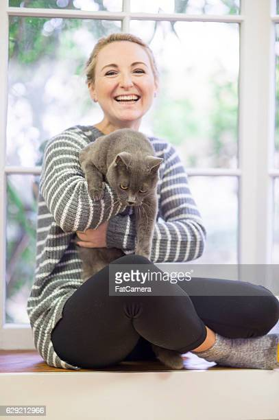 Young adult female laughing while holding her kitty
