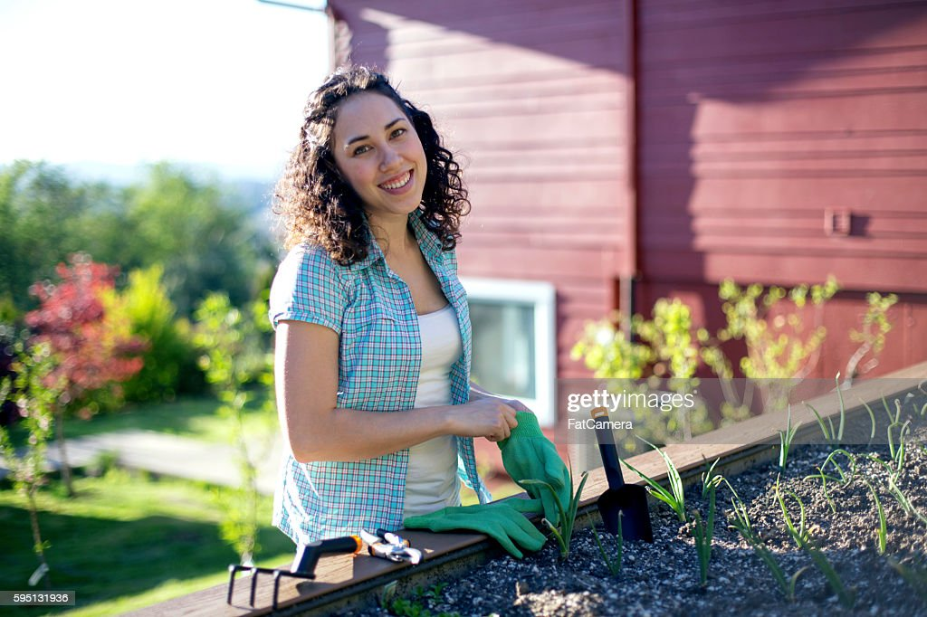 Young adult female putting on garden gloves