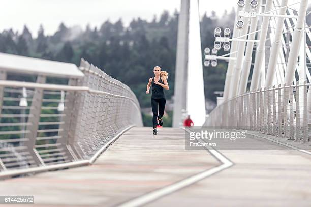 Young adult female running across a bridge
