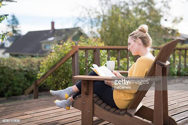 Young adult female sitting on porch drinking tea and reading