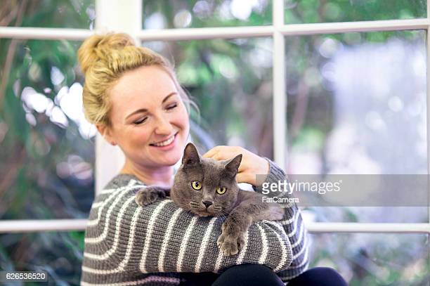 Young adult female smiling while petting her grey house cat