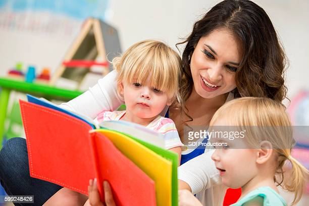 Young adult female teacher reading a book to two preschoolers