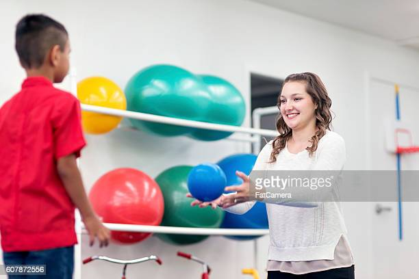 Young adult female therapist tossing balls to a young patient
