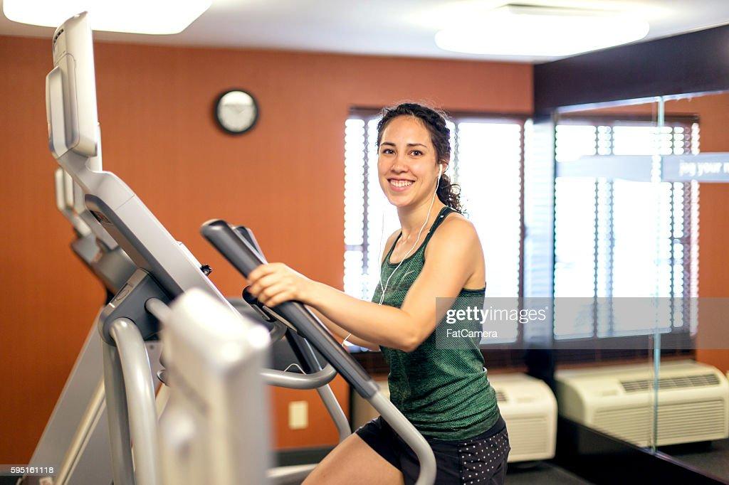 Young adult female using elliptical machine