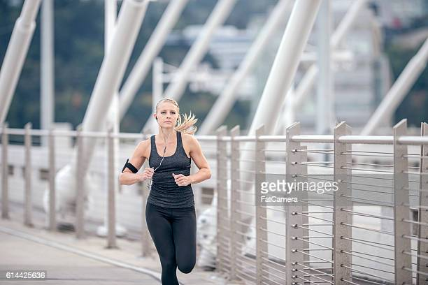Young adult female wearing headphones and running across a bridge
