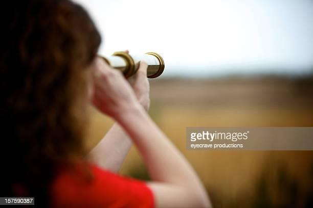 Adulto joven mujer con telescopio de latón