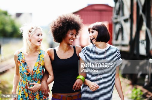 young adult females walking arm in arm