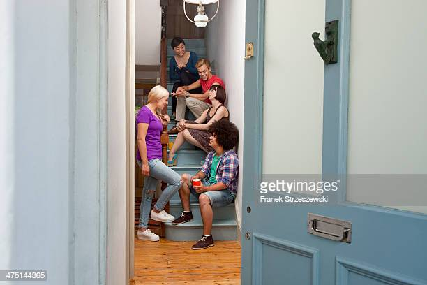 Young adult flatmates chatting on stairs