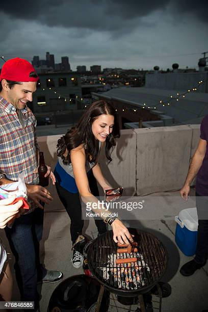 Young adult friends barbecuing at rooftop party