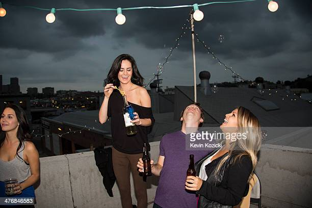 Young adult friends blowing bubbles at rooftop party