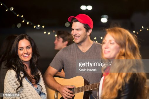 Young adult friends enjoying guitar music at rooftop party : Stock Photo