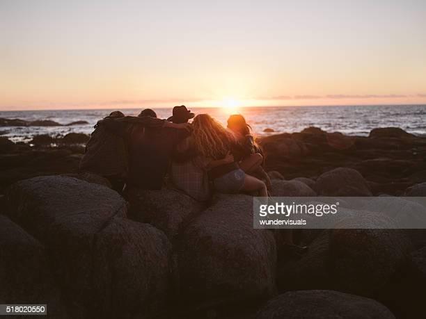 Junge Erwachsene Freunde umarmen auf einen Sonnenuntergang auf dem Meer